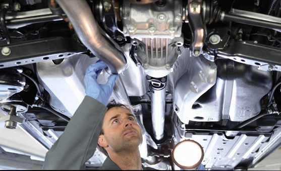 Technician checking exhaust - Exhaust repairs woking